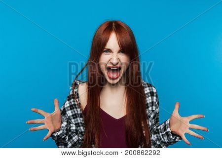 Mad screaming woman on blue background. Rage emotion. Evil young female shouting, furious feelings, conflict person, aggression concept