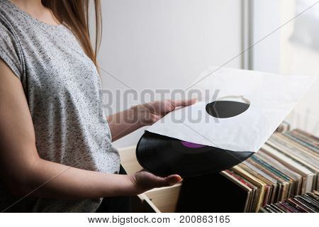 Choosing retro vinyl records in music shop. Old school background. Unrecognizable woman, modern hipster style