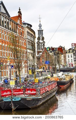 AMSTERDAM, NETHERLANDS - MARCH 30, 2017  Boat Bicycle Parking Lot Munttoren Flower Market Singel Canal Amsterdam Holland Netherlands. Munttoren tower is part of the old Amsterdam City Wall