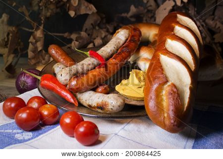 Bavarian White And Red Sausages With Mustard, Bavarian Buns And Pretzels At The Table. October Fest