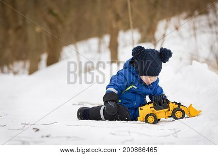 Portrait of cute little toddler sitting on snow and playing with his yellow tractor toy in the park. Child playing outdoors. Happy boy with construction toy. Lifestyle concept