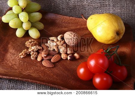 Fresh organic fruits and vegetables on wooden Serving tray. Assorted apple, pear, grapes, tomatoes and nuts