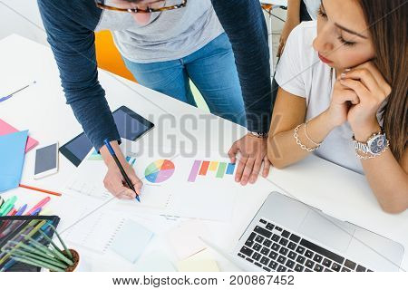 Crop anonymous man working with diagrams and showing results to young female colleague at desktop.