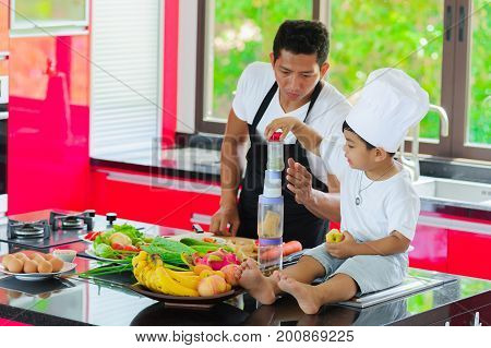 Private Thai Chef Cooking, His Little Son In Chef's Hat Nearby Sitting On The Table In A Modern Styl