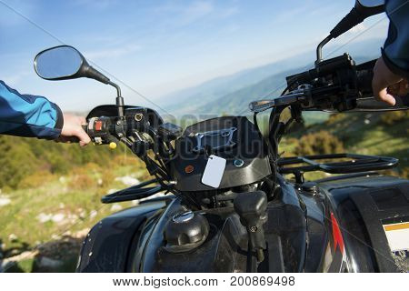 Young man on quad bike on a countryside trail. View from a quad bike