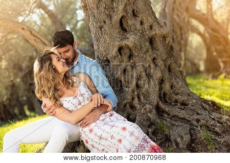 Loving young couple standing by trees at olive trees.