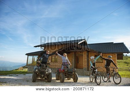 Group of friends is about to start adventure on mountain bikes and atv quad bikes in front of mountain house