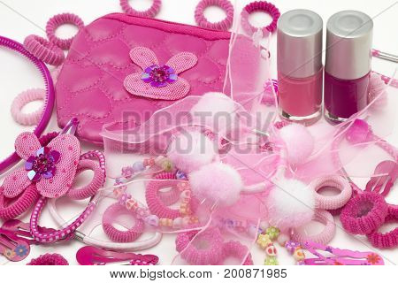 Pink fashion girly hair and nail accessories: clips, band and ribbons, pins and bow. Teenager hair clippers and grips. Little girl, girlie feminine fashion style. Nail polish bottles, cosmetic bag