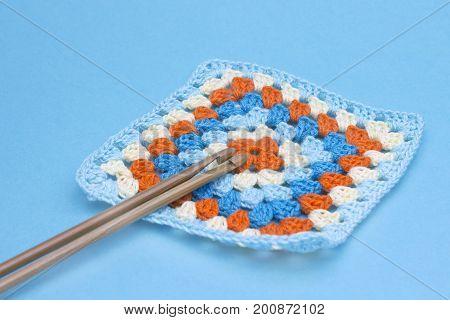 Crochet handmade granny square and hooks . The beginning of bright plaid, blanket. Colorful original crochet handmade craft work. Homemade creative craft