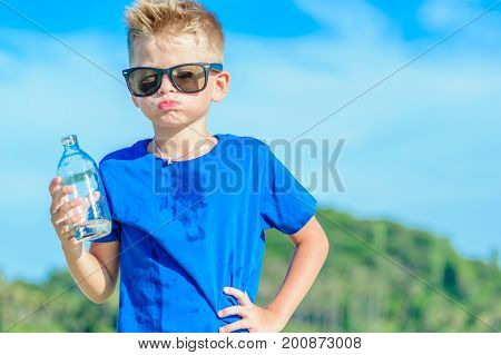 Portrait of a thirsty handsome boy in sunglasses drinking water on the desert tropical beach poster