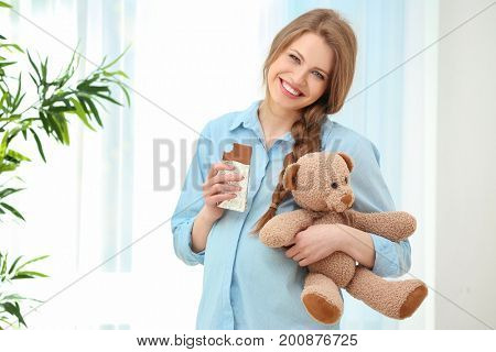 Emotional pregnant woman holding toy and eating chocolate. Pregnancy hormones concept