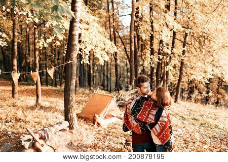 autumn camping. happy couple hugging and two under one warm blanket. making tea or coffee. warm drinks. metal teapot and cups