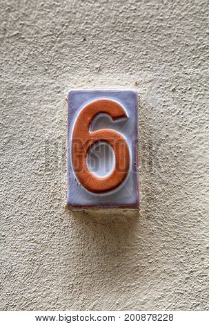 Weathered house number six(6) on a old plaster wall