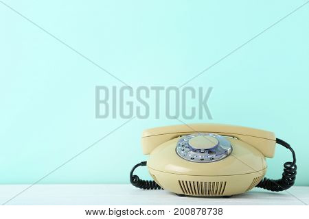 Beige retro telephone on white wooden table