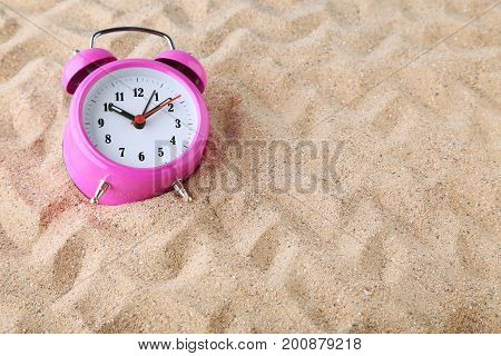 Pink alarm clock on the beach sand