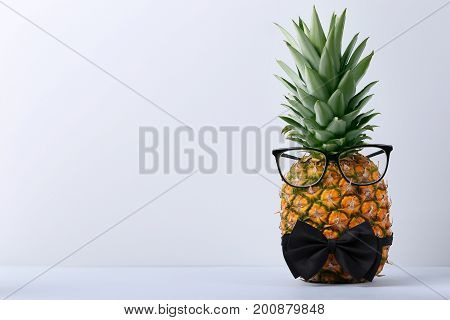 Ripe pineapple with glasses and bow tie on grey background