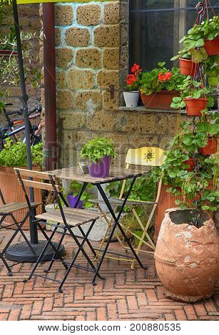 Beautiful small outdoor cafe with flower pots in Tuscany, Italy