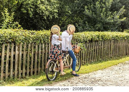 Young couple with bike tandem in park. Young people hold their hats in their hands, closing their faces.