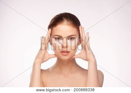 Beautiful woman on a light background in patches for eyes, facial treatment, portrait.