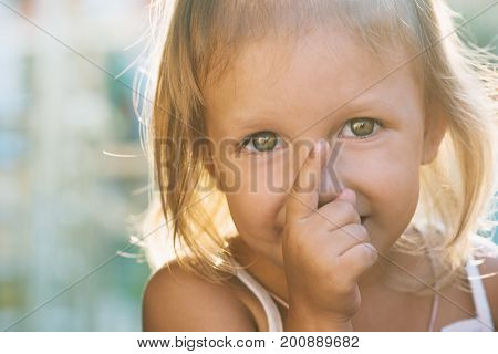 Portrait of a little girl with big beautiful eyes is pointing upwards