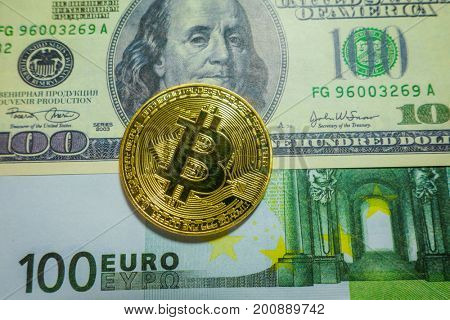 Golden bitcoin coin on the one hundred dollars and euro banknotes. Macro. Cryptocurrency concept