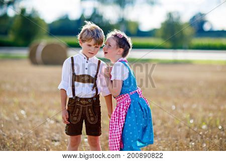 Two kids in traditional Bavarian costumes in wheat field. German children during Oktoberfest. Boy and girl play at hay bales during summer harvest time in Germany