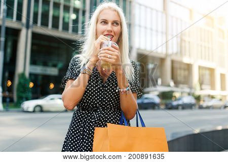 Photo of blonde with drink, with purchases near buildings in city during day