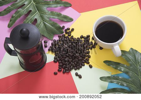 Top view flat lay of coffee cup with french press coffee beans leaves on color background.