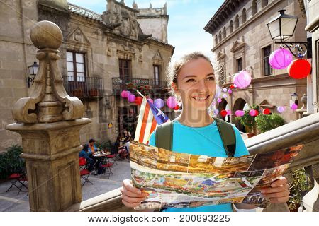Travel in Spain. Tourist holding travel map. Smiling girl walking along spanish streets in Valencia