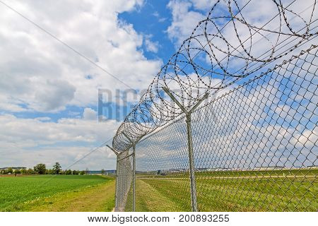fence with barbed wire green landscape and blue sky with clouds