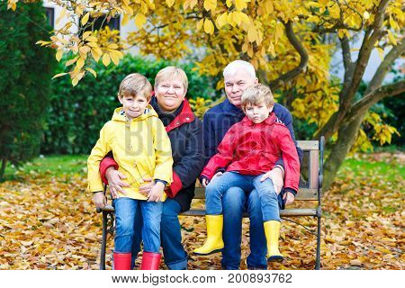 Grandfather, grandmother and two little kid boys, grandchildren sitting in autumn park. Happy family enjoying time together. Friends, love, relationship between grandsons and senior parents.