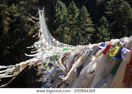 Suspension Bridge Over The Mountain Gorge In Sagarmatha National Park, Himalayas, Nepal. Tibetan Pra