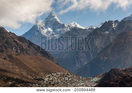 Ama Dablam Mountain In Sagarmatha National Park, Himalayas, Nepal With Mountain Village Beneath It.