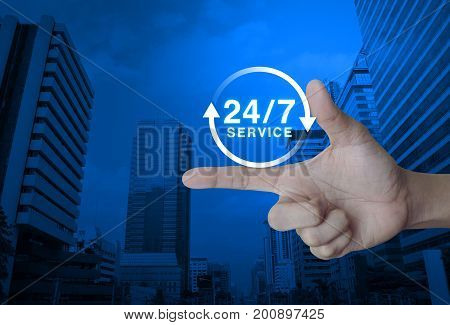 24 hours service icon on finger over modern office city tower Full time service concept