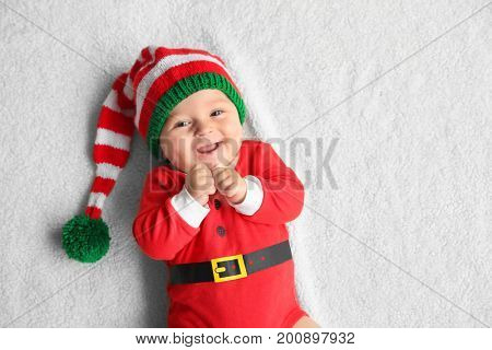 Cute little baby in Santa costume lying on soft fabric