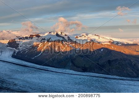 Glacier River Going Down The Volcano Mountain On Sunset. Southern Iceland. Amazing Glacier Landscape