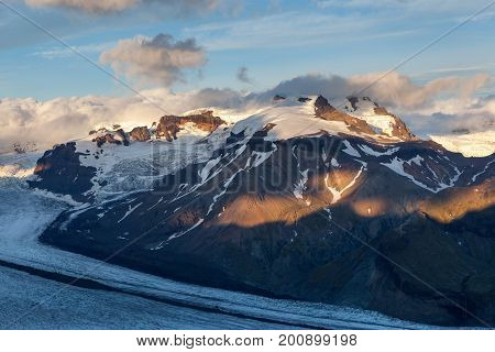 Glacier River Going Down The Volcano Mountain On Sunset. Southern Iceland. Beautiful Glacier Landsca