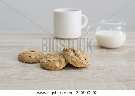 Oat meal raisin cookies and coffee with milk on the wood table.