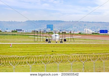 Airplane at ground on its way to runway before takeoff - green meadow with fence in front