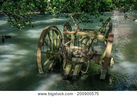 Old wooden wagon rusty and broken stranded in a waterhole
