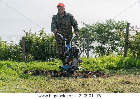 A Man Digs A Garden With A Cultivator