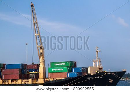 Labuan,Malaysia-Aug 2,2017:A large cargo container ship with ship cranes in the port of Labuan island,Malaysia.The abolishment of cabotage policy is set to benefit this duty-free-island economically