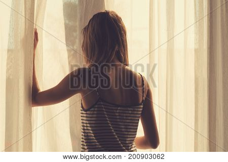 Lonesome girl holding a curtain the room.