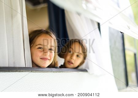Children are looking through caravan or camper motorhome window. Twin sisters are enjoying vacation travelling and camping looking through old camper caravan window.