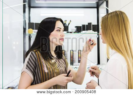 Young pretty woman chosing color cosmetic and beauty consultant in shop or beauty salon