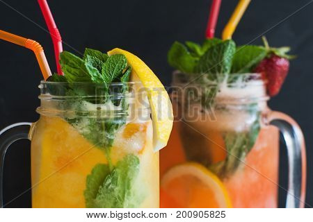 Close up fresh cocktails in glass jar on black background for satisfying thirst. Orange and strawberry cold drink with mint and ice, refreshment in hot weather