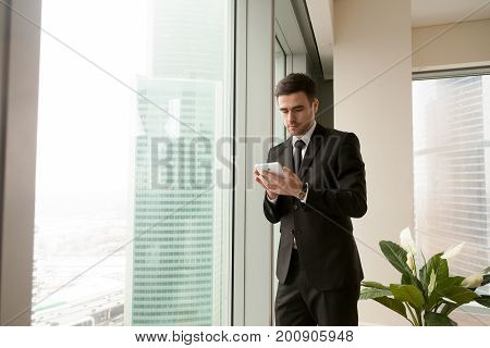 Serious businessman holding tablet standing near big office window, using business apps for organizing meetings, making payments, planning daily tasks, reading news, monitoring realtime market data