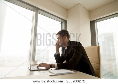 Smiling businessman talking on mobile sitting at office desk with laptop, happy boss making answering call, negotiating with client, contacting customer service, having pleasant phone conversation