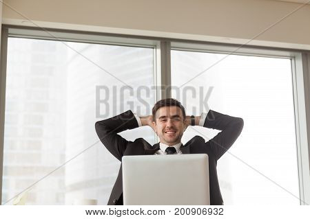 Relaxed happy businessman sitting with hands behind head at office desk, looking at laptop in front of him, satisfied with work done, time for break, using software to simplify daily business tasks