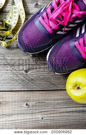 Sneakers, centimeter, green apple. Weight loss, healthy lifestyle concept with copyspace